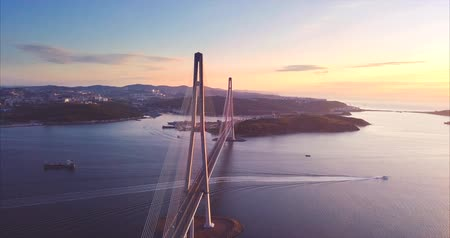 urbanística : Flying along the Russky Bridge, the worlds longest cable-stayed bridge, and the Russky Island in the Great Gulf in the Sea of ??Japan. Aerial. Sunrise. Vladivostok, Russia