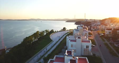 элита : Flying above a new elite residential area in Vladivostok, Russia. It is located on the bank of the Sea of ??Japan. Aerial view of Patrokl bay. People walk along the quay. Sunset Стоковые видеозаписи