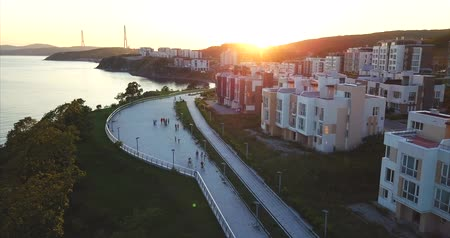 элита : Aerial view of a new elite residential area in Vladivostok, Russia. It is located on the bank of the Sea of ??Japan (Patrokl bay). People walk along the quay. Sunset