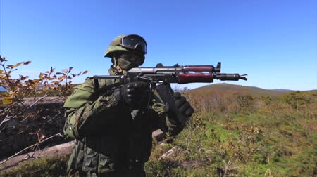 mořský : Fast tactical reloading of rifle. Soldier reloading AK rifle. Hills and sea on background Dostupné videozáznamy