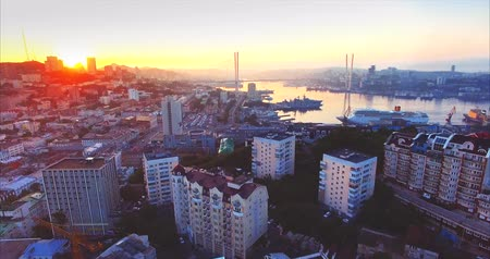 urbanística : Flying above Vladivostok city center and residential area. Aerial view of high buildings roofs. Golden Horn harbor and Golden Bridge are on the background. Early morning, sunrise. Russia Vídeos