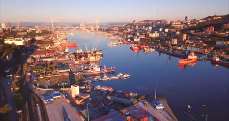Flying above the Golden Horn harbor, a sheltered horn-shaped bay of the Sea of ??Japan. Aerial view of the different ships moored here and Vladivostok city. Beautiful sunrise. Russia
