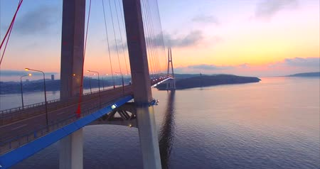 Flying along the cable-stayed Russian Bridge across the Eastern Bosphorus strait on the way to Russian island in Vladivostok, Russia. Aerial view. Early morning. Lights are still on, no cars.
