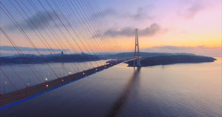 Flying backwards along the cable-stayed Russian Bridge across the Eastern Bosphorus strait on the way to Russian island in Vladivostok, Russia. Aerial view. Early morning. Lights are still on Vídeos