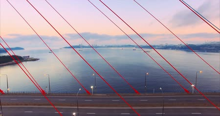 Flying slowly sideways and aerial view of the cable-stayed Russian bridge in Vladivostok, Russia. Early morning. Lights are on