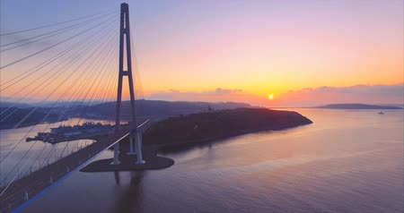 Aerial zooming out ascending view of the Russian island and cable-stayed bridge across the Eastern Bosphorus strait in Vladivostok, Russia. Beautiful sunrise
