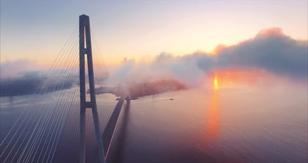 Aerial view of the cable-stayed Russian Bridge across the Eastern Bosphorus strait. Russian island and great red sunrise are behind the clouds. Picturesque view. Vladivostok, Russia Vídeos