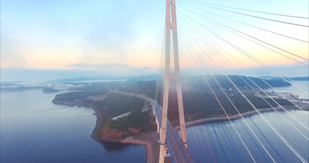 Flying high through clouds, aerial view of cable-stayed Russian Bridge across the Eastern Bosphorus strait and Russian island in Vladivostok, Russia. Early morning. Sunrise