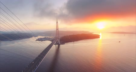 Flying backwards, aerial view of the Russian island and cable-stayed Russian Bridge across the Eastern Bosphorus strait in Vladivostok, Russia. Amazing bright sunrise