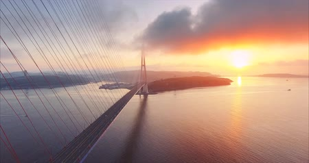 Flying backwards, great aerial view of the Russian island and the cable-stayed Bridge across the Eastern Bosphorus strait in Vladivostok, Russia. Amazing bright sunrise