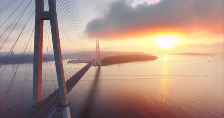 Flying along, great aerial view of the Russian island and the cable-stayed bridge across the Eastern Bosphorus strait in Vladivostok, Russia. Amazing bright sunrise