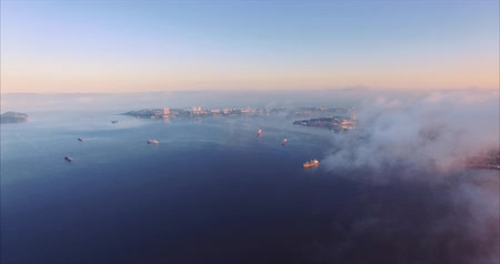 Aerial view through clouds of Vladivostok coastline, harbors and bays and ships. Beautiful blue water in early morning. Russia