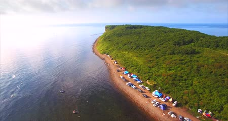 Flying backwards, aerial view of the coast, full of tourists cars and camps. Vyatlina cape, situated on the South-East part of the green island. Russia, Vladivostok Vídeos