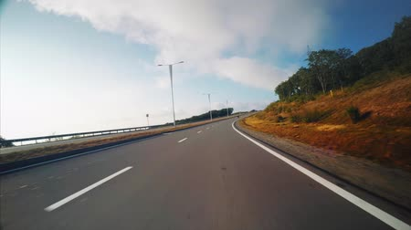 View from the car: driving fast along the road in Russian island. Vladivostok, Russia. Sunny morning Vídeos