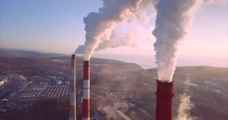 Aerial panoramic view of Central Heating and Power Plant chimneys with steam rising from them. Vladivostok, Russia. Sunrise