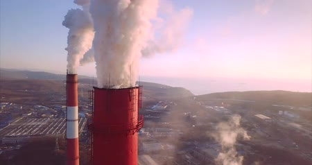 Great aerial panoramic view of Central Heating and Power Plant chimneys with steam rising from them. Vladivostok, Russia. Sunrise