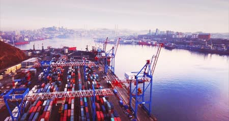 backwards : VLADIVOSTOK, RUSSIA-DECEMBER 2, 2017: Flying backwards above many colorful containers in the commercial port in the morning .. Aerial view. The city is on the background Stock Footage