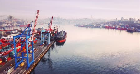 container terminal : VLADIVOSTOK, RUSSIA-DECEMBER 2, 2017: Aerial view of Commercial port with containers, cranes, ships. Morning city is on the background Stock Footage