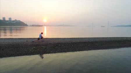 plivat : Young man doing physical exercises on Tokarevsky spit at beautiful summer sunrise Dostupné videozáznamy