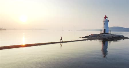 willpower : Aerial view of man running fast along the spit at sunrise. Vladivostok, Russia Stock Footage