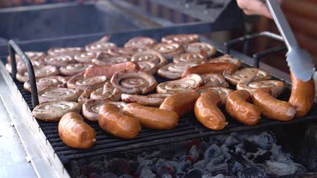 barbequing : Steaks and sausages on the grill with flames. Turn the meat over. Food in nature