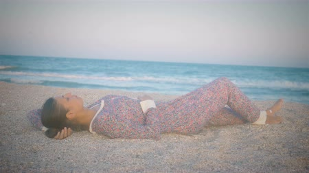 Girl in pajamas lying on the beach, the seaside at sunset