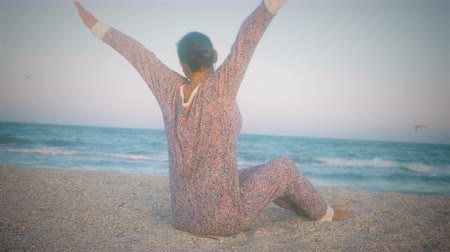 Girl in pajamas stretches, sitting on the beach before sunset