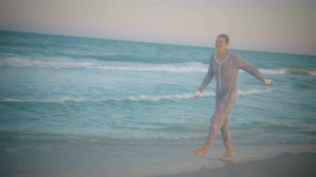 Smiling girl in pajamas runs skipping along the picturesque sea coast Stok Video