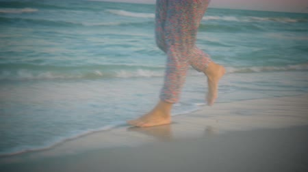 пижама : Girl in pajamas walking in shallow water along the coast at sunset Стоковые видеозаписи