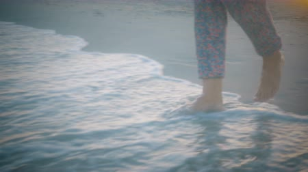 Close up girls feet in colorful clothes entering the surf