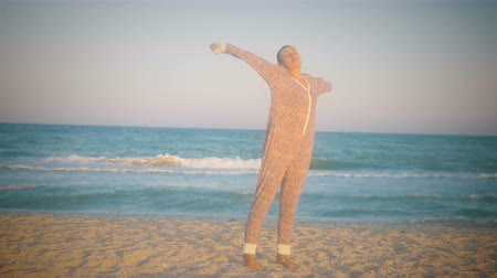 girl in pajamas stretching, standing on the sea coast at sunset
