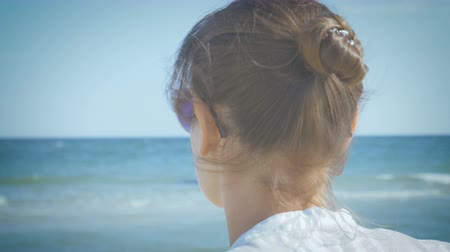 Girl in a white shirt taking off her sunglasses, looking around and smiling, sitting on the seashore. Close-up