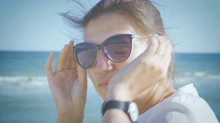 Girl in a white shirt putting on sunglasses and smiling while sitting on the seashore. Close-up