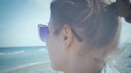 Girl in sunglasses peering into the sea far in anticipation of someone  something sitting on the beach. Close-up