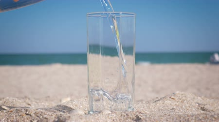 Glass standing in the sand filling with drinking water on the beach on the background of the sea. Close-up Stok Video