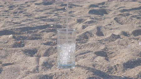 Glass standing in the middle of the sand filling with fresh drinking water