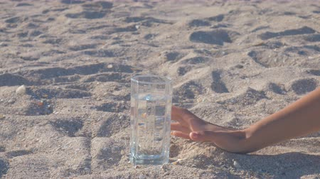 sede : Womans hand reaching for a glass filled with water standing in the middle of the sand