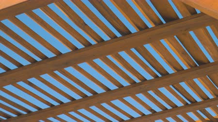 tenda da sole : A wooden canopy against a clear sky background on a sunny day. Geometry in space, intersecting lines. Shades of yellow on a blue background Filmati Stock
