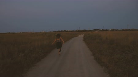 Girl in a waving dress jumping, spinning and laughing on the road at the summer field at sunset Stok Video