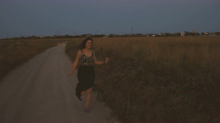 Birl in a waving dress gaily runing and laughng on the road at the summer field at sunset