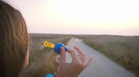 Girl in bright clothes blowing the soap bubbles in the wind and smiling in the evening against the backdrop of the road to the field