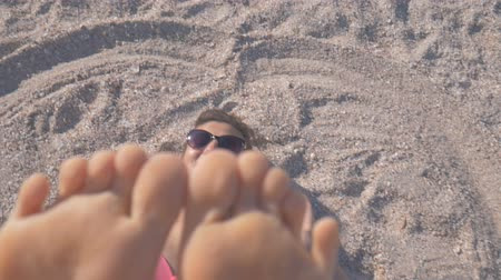 Close-up of feet. Girl in a swimsuit lying on the beach and laughing playfully moving her toes Stok Video