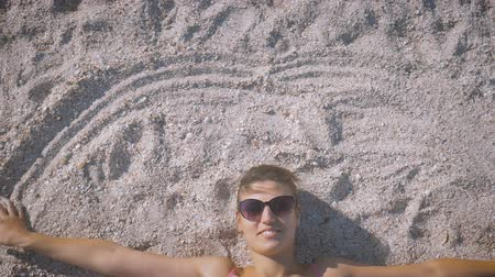 csatlakozott : Girl in a swimsuit and sunglasses lies on the beach, smiling and making her hands circles on the sand