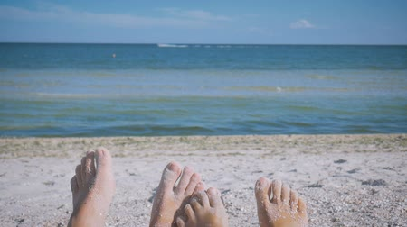 Mens and womens feet in the sand against the sea playful and fun wiggling fingers. Couple in love. Romance