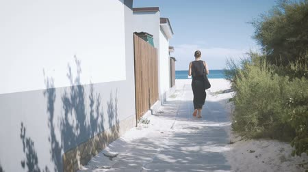Girl in black with a beach bag goes along the path towards the sea. View from the back