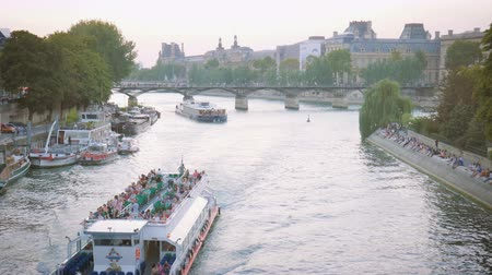 Pleasure boats cruisingl on the Seine in the evening in Paris, people sitting on the waterfront