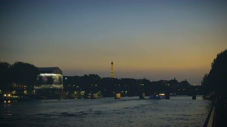 Pleasure boats cruising on the Seine in the evening in Paris, Eiffel Tower view