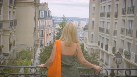 A woman watches Paris from a viewing platform on the Montmartre Stock mozgókép