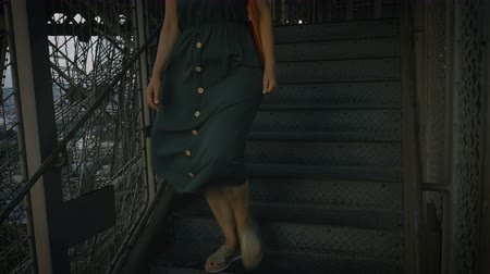A woman descends the stairs of the Eiffel Tower evening