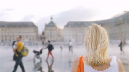 Бордо : A woman is standing on a Miroir deau in the center of Bordeaux people are walking along the central square in the middle of the fog